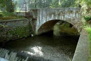 Barokní kamenný most se klene přes Výrovku v Radimi